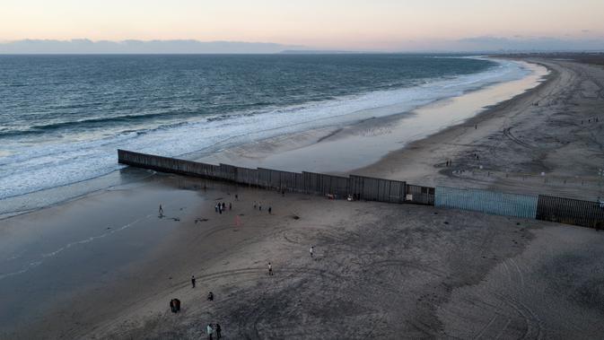 Orang-orang berjalan di pantai dekat perbatasan AS dan Meksiko di Tijuana, Meksiko, Jumat (23/11). Selama beberapa pekan terakhir pemerintahan AS telah berusaha menahan laju rombongan imigran masuk ke negaranya. (AP Photo/Rodrigo Abd)#source%3Dgooglier%2Ecom#https%3A%2F%2Fgooglier%2Ecom%2Fpage%2F%2F10000