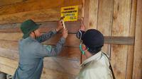 Petugas memasang tanda di pondok diduga milik perambah hutan Suaka Margasatwa Giam Siak Kecil. (Liputan6.com/Dok BBKSDA Riau)