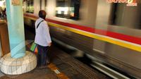 Tampak seorang  wanita yang sedang berdiri  menunggu kereta Commuter Line datang (Liputan6.com/  JohanTallo)