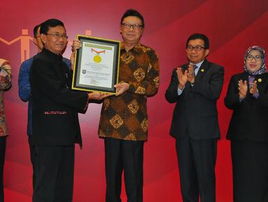 Mendagri Tjahjo Kumolo menerima piagam rekor MURI usai melakukan penandatangan kerja sama pemanfaatan data kependudukan dengan 100 pelaku usaha Bursa Efek Indonesia (BEI) di Gedung BEI, Jakarta, Selasa (22/11). (Liputan6.com/Angga Yuniar)