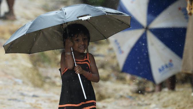 Seorang anak pengungsi Rohingya berjalan menggunakan payung saat hujan di kamp pengungsi Kutupalong, Ukhia (12/9/2019). Kamp ini didirikan secara tidak resmi pada tahun 1991, setelah ribuan orang Rohingya melarikan diri dari Operasi Pyi Thaya yang dilancarkan militer Burma. (AFP Photo/Munir Uz Zaman