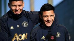 Pemain Manchester United, Marcos Rojo dan Alexis Sanchez, tersenyum saat latihan jelang laga 16 besar Liga Champions di Kompleks Carrington, Manchester, Senin (11/2). MU akan menjamu PSG pada leg pertama di Stadion Old Trafford. (AFP/Franck Fife)