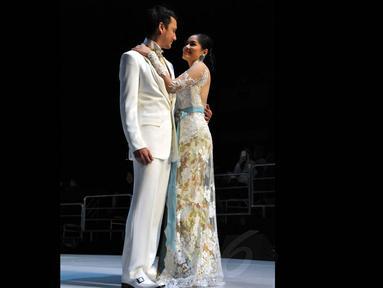 Pasangan Christian Sugiono dan Titi Kamal membawakan karya Anne Avantie yang betema putih, Jakarta, (3/9/14). (Liputan6.com/Panji Diksana)