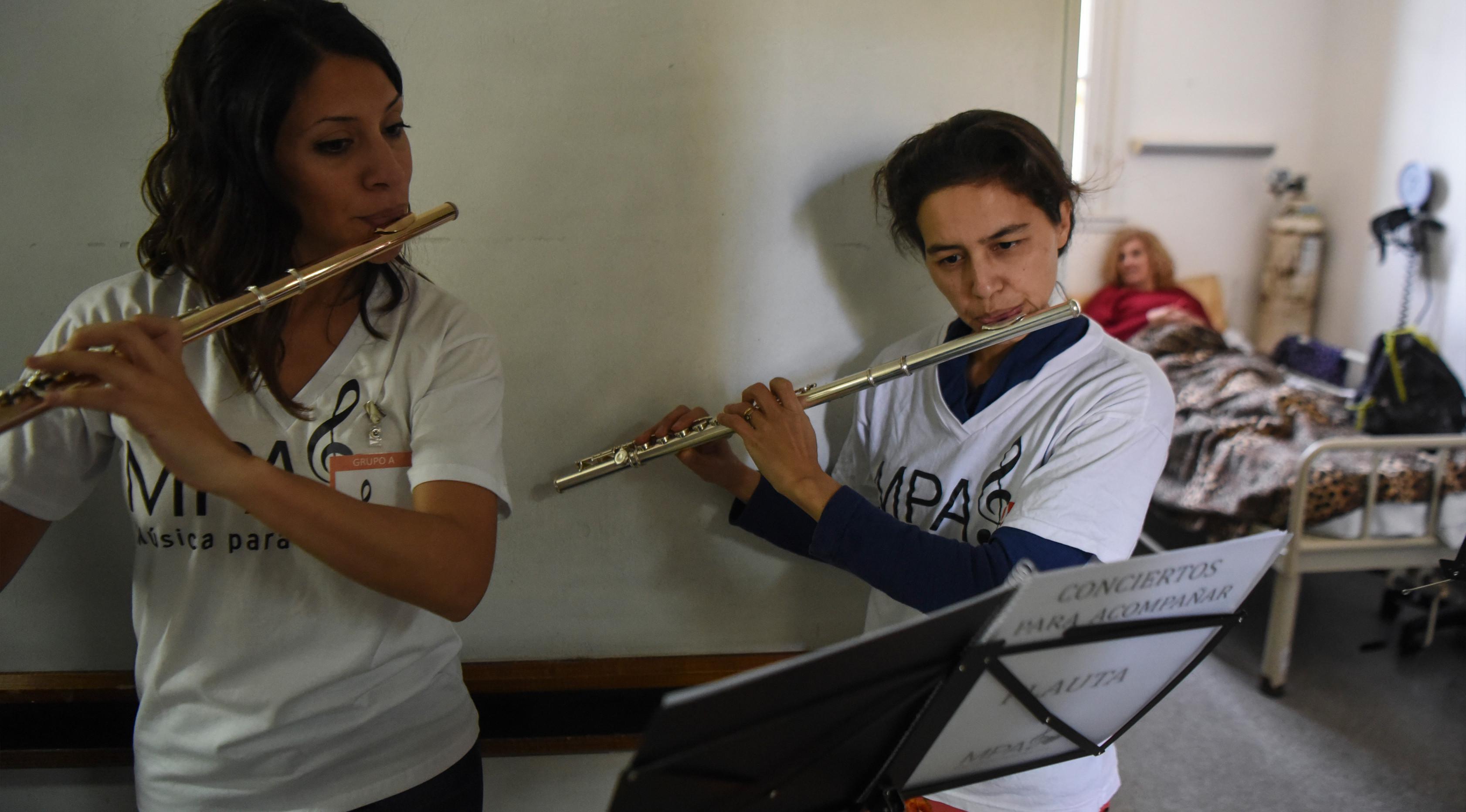Dua orang relawan dari Musica Para el Alma memainkan alat musiknya di Rumah Sakit Alvarez di Buenos Aires, Argentina (12/6). Mereka juga sering tampil di sekolah pendidikan khusus, panti jompo dan institusi publik lainnya. (AFP Photo/Eitan Abramovich)