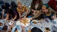 Orang-orang berbagi makanan dengan yang lain saat berbuka puasa bersama di dekat Taksim Square, Istanbul, Turki, Rabu (16/5). (Yasin AKGUL/AFP)
