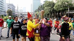 Dalam aksinya, mereka membawa obor perdamaian untuk memperingati Hari Toleransi Internasional, Jakarta, Minggu (16/11/2014). (Liputan6.com/Faizal Fanani)