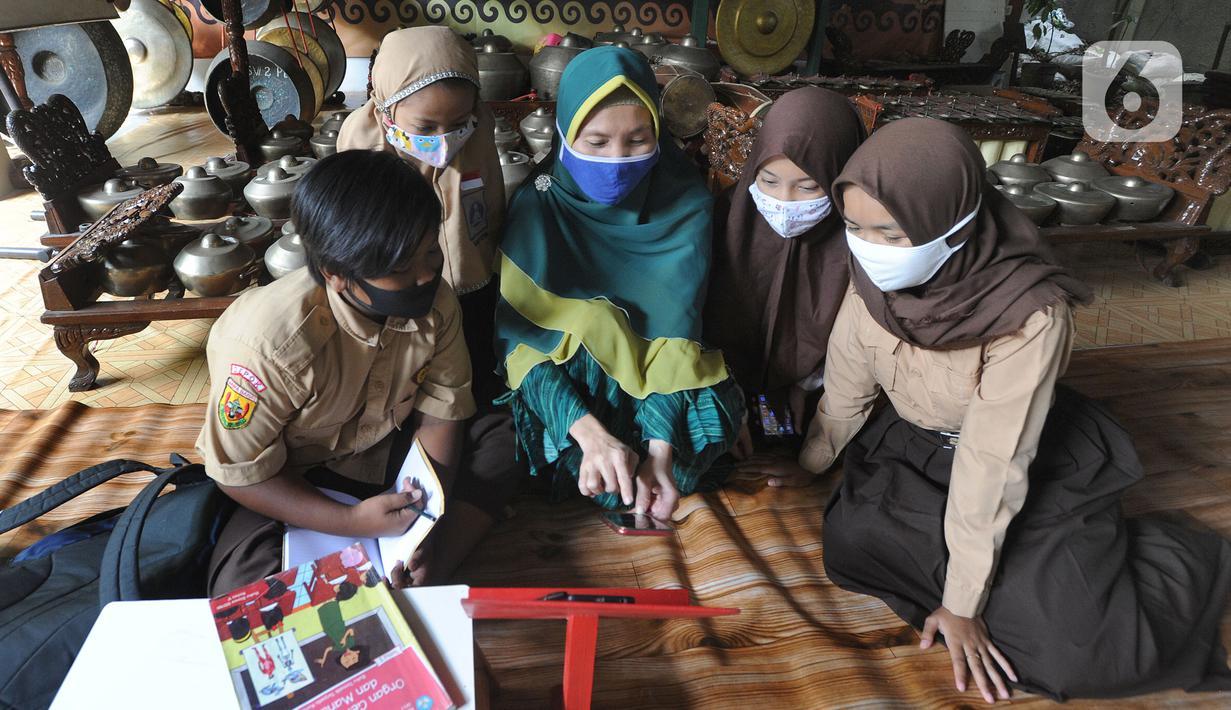 Siswa belajar secara daring menggunakan fasilitas wifi gratis di Perumahan Pondok Mulya I, Beji, Depok, Jawa Barat, Rabu (29/7/2020). Fasilitas tersebut disediakan oleh Sri Wiwoho untuk siswa sekitar perumahan. (merdeka.com/Arie Basuki)