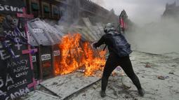 Seorang demonstran melemparkan bensin ke barikade polisi yang melindungi Istana Nasional selama pawai untuk memperingati Hari Perempuan Internasional dan protes terhadap kekerasan gender di Mexico City, Meksiko, Senin (8/3/2021). (AP Photo/Ginnette Riquelme)