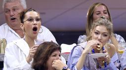 Keseruan Gigi Hadid bersama Bella Hadid (kiri) menyaksikan perempat final tunggal putri antara petenis AS, Serena Williams melawan Karolina Pliskova dari Republik Ceko pada hari ke-9 turnamen AS Terbuka di New York, Selasa (4/9). (Greg Allen/Invision/AP)