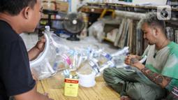 Bucek (kanan) dan Mamay menyelesaikan pembuatan face shield di workshopnya di kawasan Bekasi, Jawa Barat, Rabu (3/6/2020). Face shield tersebut dijual dengan harga Rp 20 ribu hingga Rp 25 ribu. (Liputan6.com/Faizal Fanani)