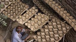 Seorang perajin tembikar membuat lampu dari tanah liat untuk menyambut Diwali, festival cahaya bagi umat Hindu, di New Delhi, India (8/11/2020). Umat Hindu di seluruh penjuru India menghias rumah mereka dengan lampu dari tanah liat dan menyalakan lilin untuk merayakan Diwali. (Xinhua/Javed Dar)