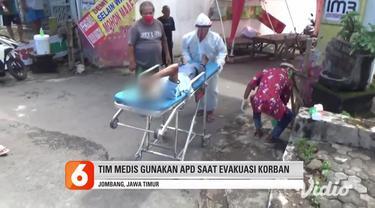 Seorang pria paruh baya tak sadarkan diri di pinggir jalan Soekarno-Hatta, Desa Kepuhkembeng, Kecamatan Peterongan, Jombang, Jawa Timur, Jumat siang. Warga di sekitar tak berani menolong khawatir Covid-19, petugas medis menolong dengan menggunakan AP...