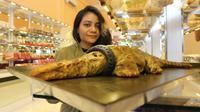 Natalia, salah satu pembeli sedang berposes bersama roti buaya berkalung ban di toko roti di Jalan RE Martadinata, Palu. (Liputan6.com/ Heri Susanto)