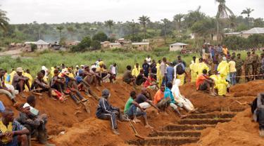 Relawan bersiap memakamkan massal korban banjir dan tanah longsor di sebuah pemakaman di Sierra Leone, Freetown, (17/8). Pemerintah setempat telah mengubur 350 orang yang tewas akibat musibah tersebut. (AP Photo/Kabba Kargbo)