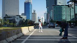 Seorang wanita berfoto dengan latar belakang Jalan MH Thamrin yang masih ditutup oleh aparat keamanan di Jakarta, Jumat (24/5/2019). Ditutupnya Jalan MH Thamrin terkait unjuk rasa menolak hasil Pemilu 2019 dimanfaatkan sebagian warga untuk berfoto. (Liputan6.com/Immanuel Antonius)