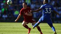 Bek Liverpool, Andrew Robertson berusaha melewati kawalan pemain Cardiff City pada laga lanjutan Premier League yang berlangsung di Stadion Millenium, Cardiff, Minggu (21/4). Liverpool menang 2-0 atas Cardiff City. (AFP/Geoff Caddick)
