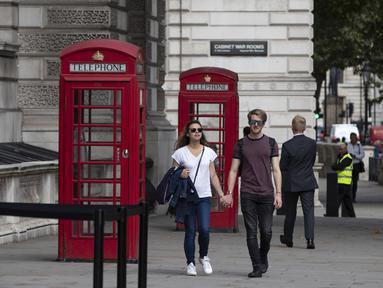 Orang-orang berjalan melewati bilik telepon umum di pusat Kota London, Inggris (8/9/2020). Angka resmi terbaru Inggris pada Selasa (8/9) menunjukkan bahwa korban meninggal akibat COVID-19 di negara tersebut telah mencapai 57.400. (Xinhua/Han Yan)