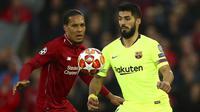 Bek Liverpool, Virgil Van Dijk, berebut bola dengan striker Barcelona, Luis Suarez, pada laga semifinal Liga Champions 2019 di Stadion Anfield, Selasa (7/5). Liverpool menang 4-0 atas Barcelona. (AP/Dave Thompson)