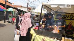Pengunjung membeli makanan pada Festival Tugu Pancoran di Jakarta, Minggu (1/12/2019). Festival Tugu Pancoran yang digelar setiap setahun sekali ini indetik dengan budaya betawi. (Liputan6.com/Herman Zakharia)