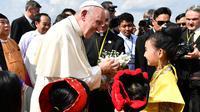 Paus Fransiskus menerima bunga saat disambut anak-anak di Bandara Internasional Yangon, Myanmar (27/11). Kedatangan Paus juga disambut dengan pakaian tradisional etnik, lambaian bendera dan tari-tarian di bandara Yangon. (AFP Photo/Vincenzo Pinto)