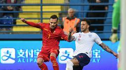 Marko Vesovic mencoba melewati pemain Inggris, Kyle Walker pada laga kedua Kualifikasi Piala Eropa 2020 yang berlangsung di Stadion Pod Goricom, Podgrica, Selasa (26/3). Timnas Inggris menang 5-1 atas Montenegro. (AFP/Savo Prelevic)