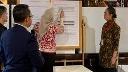 Petugas KPPS Luar Negeri mencatat perolehan suara saat penghitungan suara Pemilu 2019 yang dikirimkan melalui pos maupun yang dicoblos langsung di TPS oleh pemilih WNI, di KBRI Washington DC, Kamis (18/4). Jokowi meraih 1113, sementara pasangan Prabowo-Sandi meraih 352 suara. (Liputan6.com/HO/Butet)
