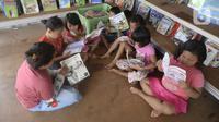 Anak-anak membaca buku di Taman Baca milik Karang Taruna Tunas Karya, Kampung Cibarengkok, Desa Pengasinan, Gunung Sindur, Kabupaten Bogor, Senin (24/8/2020). Taman Baca yang didirikan pada masa pandemi COVID-19 ini untuk hiburan serta meningkatkan pengetahunan anak-anak. (merdeka.com/Dwi Narwoko)