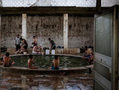 Pengunjung menikmati kolam renang air hangat dari belerang di Hamam Alli, Mosul, Irak, (27/4). Sebelum ISIS mengambil alih Hamam Alil pada 2014, warga Irak selalu mengunjungi spa bersejarah di selatan Mosul ini. (AP Photo/Bram Janssen)