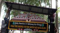 Pekerja memasang gapura menyambut tamu acara ngunduh mantu Kahiyang Ayu dan Bobby Nasution di Komplek Bukit Hijau Regency, Medan, Kamis (23/11). Rangkaian upacara adat dan resepsi Kahiyang dan Bobby dilangsungkan 24-26 November. (Liputan6.com/Johan Tallo)