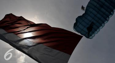 Seorang Prajurit melakukan aksi terjun Payung membawa bendera Merah Putih dalam Rangkaian Peringatan HUT TNI AU ke - 70 di Lanud Halim Perdanakusuma, Jakarta, (9/4). Sejumlah atraksi ditampilkan oleh prajurit TNI AU. (Liputan6.com/Johan Tallo)