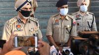 Polisi negara bagian Punjab saat berbicara kepada media di distrik Tarn Taran pada 1 Agustus 2020, setelah puluhan orang meninggal karena mengkonsumsi miras ilegal beracun (AFP Photo/NARINDER NANU)