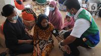 Paramedis memeriksa kesehatan pengungsi korban ledakan kilang minyak Balongan di Pendopo Kabupaten Indramayu, Senin (29/03/2021). Sekitar 900 warga saat ini mengungsi dari lima desa terdampak ledakan kilang minyak Balongan.  (merdeka.com/Arie Basuki)