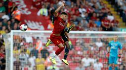 Pemain Liverpool Alex Oxlade-Chamberlain (depan) berebut bola udara dengan pemain Arsenal Ainsley Maitland-Niles (belakang) saat bertanding dalam Liga Inggris di Stadion Anfield, Liverpool, Inggris, Sabtu (24/8/2019). Liverpool menang 3-1 dan kukuh di puncak klasemen sementara. (AP Photo/Rui Vieira)