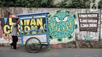 Pedagang melintasi mural bertema imbauan protokol kesehatan COVID-19 di kawasan Cakung Barat, Jakarta, Minggu (18/10/2020). Mural karya warga setempat tersebut bertujuan mengingatkan masyarakat akan pentingnya memakai masker, menjaga jarak, dan mencuci tangan. (merdeka.com/Iqbal S. Nugroho)