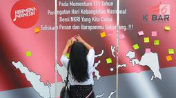 Seorang wanita menempelkan kertas berisi tulisan saat melakukan deklarasi Indonesia Bangkit saat hari kebangktian nasional ke 111 tahun di GBK, Jakarta, Senin (20/5). Tujuan deklarasi ini untuk menyegarkan kembali ingatan dan tekad merawat persatuan Indonesia. (Liputan6.com/Angga Yuniar)
