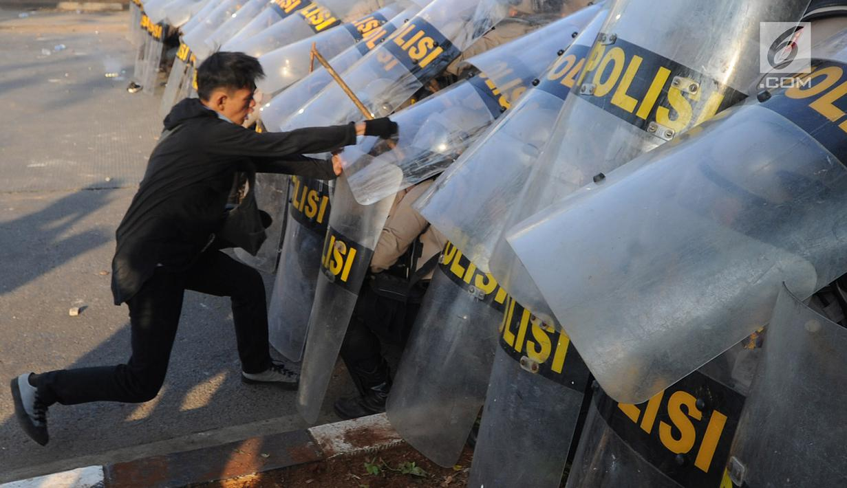Massa aksi memukul polisi yang membentuk barikade dengan tameng di dekat Gedung DPR/MPR, Jalan Gatot Subroto, Jakarta, Senin (30/9/2019). Aksi unjuk rasa dari berbagai elemen tersebut menyikapi penolakan terhadap UU KPK dan sejumlah RUU yang dinilai bermasalah. (merdeka.com/Arie Basuki)