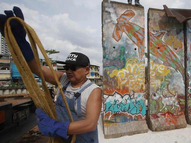 """Seniman Teguh Ostenrik saat memasang bongkahan Tembok Berlin di RPTRA Kalijodo, Jakarta, Selasa (26/9). Empat segmen pecahan Tembok Berlin dan 14 """"Patung Menembus Batas"""" untuk memperindah bekas lokalisasi Kalijodo. (Liputan6.com/Immanuel Antonius)"""