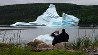 Wisatawan menyaksikan pemandangan gunung es terapung dekat King's Point, Newfoundland, Kanada, 3 Juli 2019. Gunung es terapung memberi pemandangan kontras yang unik, terutama bagi penggemar fotografi. (Johannes Eisele/AFP)