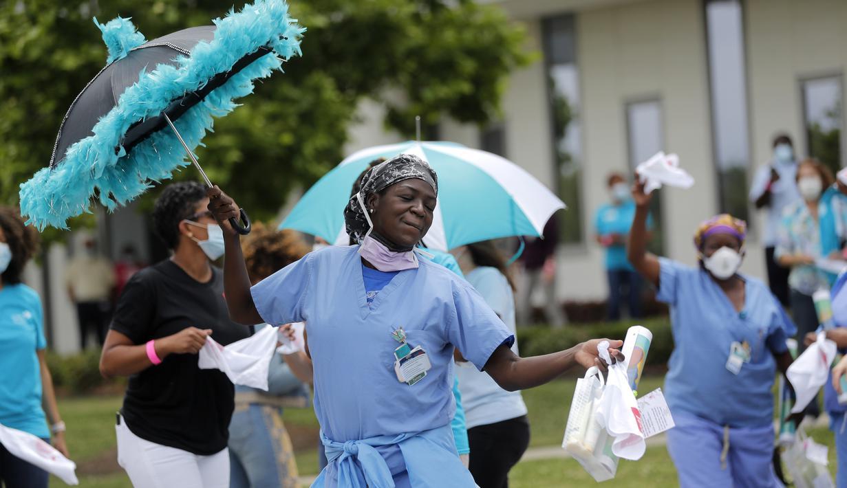 Petugas medis menari sebagai penghargaan atas perawatan untuk pasien COVID-19 di luar New Orleans East Hospital, New Orleans, Amerika Serikat, 15 Mei 2020. Serenade stimulus ini untuk memberikan dukungan moral kepada petugas medis dan pasien COVID-19. (AP Photo/Gerald Herbert)