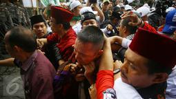 Ekspresi seorang pria yang diduga provokator diamankan dari amukan massa saat sidang kasus penistaan agama di Jakarta, Selasa (10/1). Sempat terjadi kericuhan akibat peristiwa tersebut. (Liputan6.com/Immanuel Antonius)