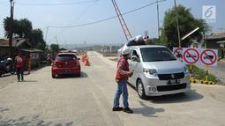 Petugas memberi arahan kepada pengguna mobil yang akan melintas di jalan fungsional Bocimi di kawasan Cigombong, Bogor (9/6). (Merdeka.com/Arie Basuki)