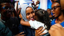 Ilhan Omar memeluk anaknya saat merayakan kemenangan putaran pertama pemilihan Distrik Kongres ke-5 di Minneapolis, AS, Selasa (14/8). Omar segera menggantikan posisi Keith Ellison dari kursi perwakilan rakyat. (Mark Vancleave/Star Tribune via AP)