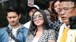 Pedangdut Dewi Perssik (tengah) ditemani suami, Angga Wijaya (kiri) dan kuasa hukumnya Hotman Paris Hutapea mendatangi Polda Metro Jaya, Jakarta, Senin (5/11). Dewi juga melaporkan manajemen yang menaungi Rosa Meldianti. (Liputan6.com/Faizal Fanani)