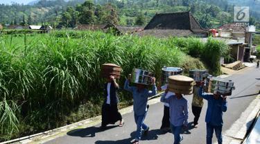 Warga membawa makanan menuju makam Desa Selo, Kabupaten Boyolali, Kamis (3/5). Tradisi ini Sebagai perayaan menyambut datangnya bulan ramadan, kemudian dilanjutkan makan bersama di pertigaan jalan desa. (Liputan6.com/Gholib)
