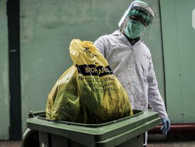 Petugas mengenakan APD saat membawa kantong berisi limbah Covid-19 ke Tempat Penyimpanan Sementara Limbah B3 di Laboratorium Kesehatan Daerah (Labkesda) DKI Jakarta, Selasa (4/8/2020). Pembuangan limbah Covid-19 dilakukan dengan proses ketat sesuai protokol kesehatan. (merdeka.com/Iqbal Nugroho)