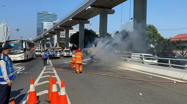 Sebuah mobil terbakar di Kilometer 5, Tol Dalam Kota Jakarta, pada Senin (26/7/2021).