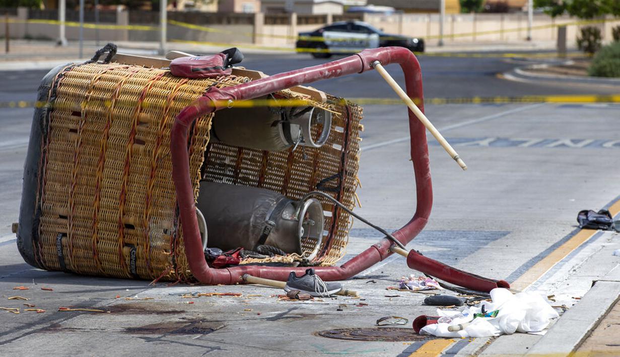 Keranjang balon udara yang jatuh tergeletak di trotoar di Albuquerque, New Mexico, Amerika Serikat, Sabtu (26/6/2021). Polisi mengatakan lima penumpang tewas setelah jatuh di jalan yang ramai. (AP Photo/Andres Leighton)