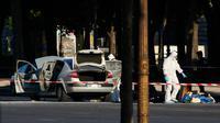 Tim penyelidik forensik melakukan olah TKP lokasi serangan di kawasan Champs Elysees, Paris, Senin (19/6). Seorang pria yang diduga terkait dengan ekstrimis menabrakkan mobilnya ke arah mobil van polisi di jalanan ikonik itu. (AP Photo/Matthieu Alexandre)