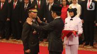 Presiden Joko Widodo atau Jokowi (kanan) memasangkan pangkat jabatan kepada Kapolri Idham Azis saat upacara pelantikan di Istana Negara, Jakarta, Jumat (1/11/2019). Idham Azis dilantik menjadi Kapolri menggantikan Tito Karnavian yang diangkat menjadi Mendagri. (Liputan6.com/Angga Yuniar)