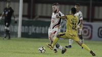 Gelandang Mitra Kukar, Danny Guthrie, berusaha melewati gelandang Bhayangkara FC, Wahyu Suboseto, pada laga Liga 1 di Stadion PTIK, Jakarta, Kamis (17/5/2018). Bhayangkara FC menang 1-0 atas Mitra Kukar. (Bola.com/M Iqbal Ichsan)